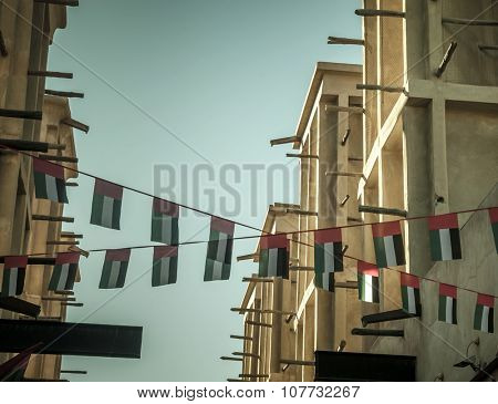 Old buildings in Dubai are decorated with bunting of UAE national flag.