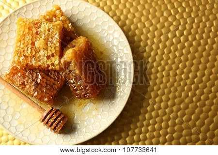 Honeycombs and wooden dipper on plate on bright background