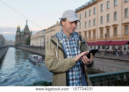 Mature tourist with a tablet in St. Petersburg, Russia