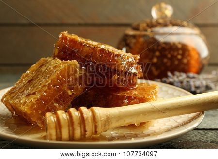 Honeycombs and wooden dipper on plate on wooden background