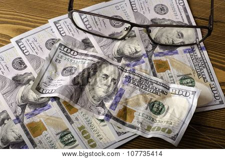 Glasses On Top Of The $ 100 Bills And Crumpled $ 100 Bill .