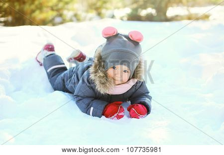 Happy Little Child Lying Playing On Snow In Winter Day