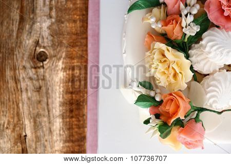 Beautiful wedding cake decorated with flowers on wooden table in the room, close up