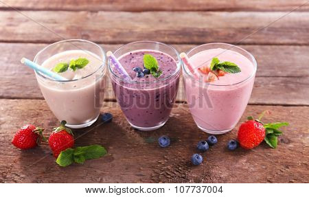 Tasty blueberry, strawberry and milk yogurts in a row decorated with berries and mint on wooden background