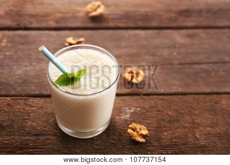 Fresh yogurt with mint and nuts on wooden background