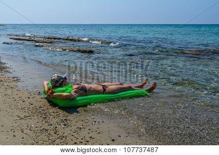Beautiful Young Woman Sunbathing On A Stone Beach On An Air Mattress.
