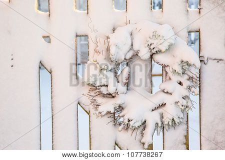 A Christmas wreath decorating a garden gate, all covered in snow.