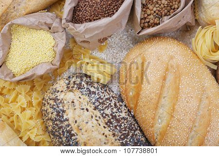 Mixed breads, macaroni and grains background, close up