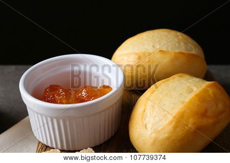 Tasty jam in bowl, crackers and fresh buns close-up