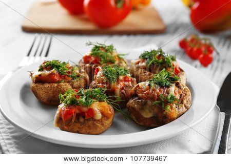 Served table with stuffed mushrooms on white wooden background, close-up