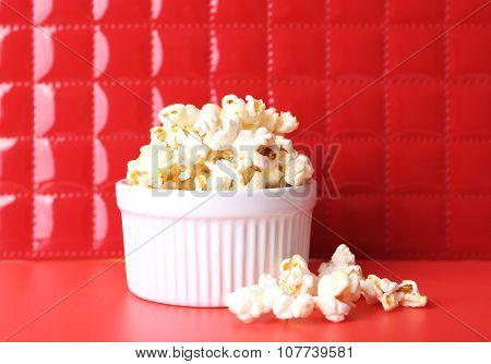 Salted popcorn on red background