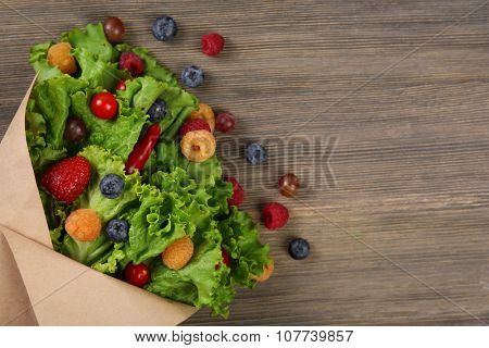Beautiful bouquet of lettuce and berries in paper sheath on wooden background