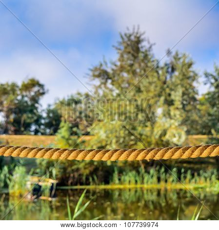 Tightrope On A Background Of Trees And Water. Horizontal Scene Of Rope, Blue Sky And Calm Lake In Th