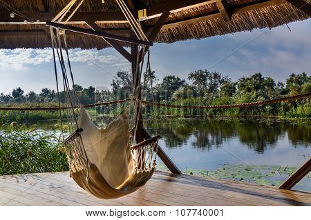 Chair Hammock In The Arbor On Nature Background. Peaceful View On The Lake From Wooden Gazebo..
