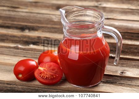 Fresh Red Tomatoes In Basket And Tomato Juice In Jug On Brown Wooden Table