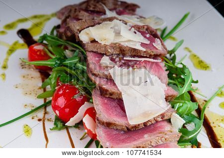 Medium rare steak served on a plate with vegetables and cheese