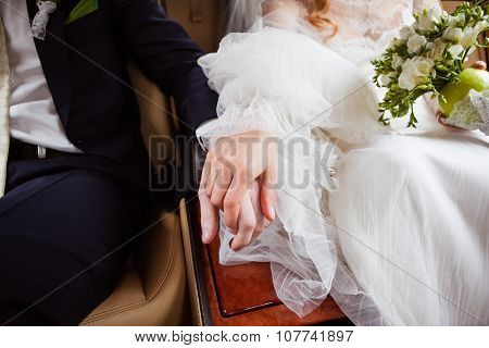 Bride And Groom Holding Hands In A Car