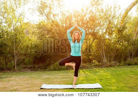Woman doing yoga poses outside in a park