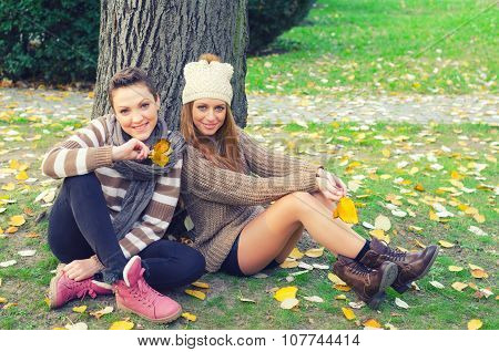Two Happy Smiling Teenage Girls Sitting In Park On Beautiful Autumn Day.