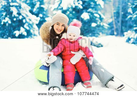 Happy Mother And Child Sitting Together On Sled In Winter Snowy Day