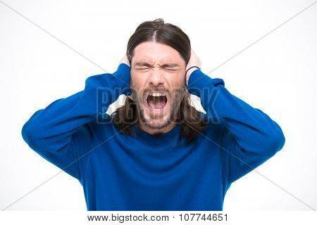 Desperate hysterical angry man with long hair closed ears by hands and screaming with opened mouth