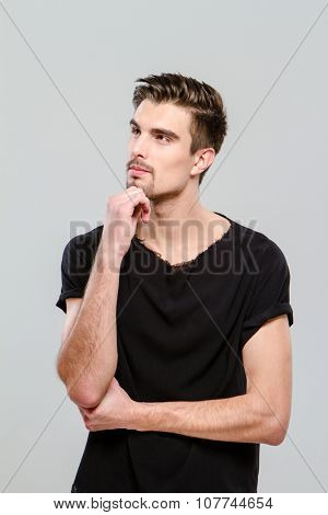 Thoughtful young handsome man in black t-shirt looking aside against white background