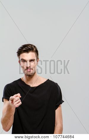 Young handsome charming guy in black t-shirt pointing on you