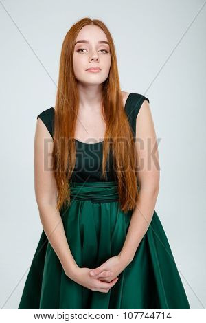 Portrait of a serious redhair woman in green dress looking at camera isolated on a white background