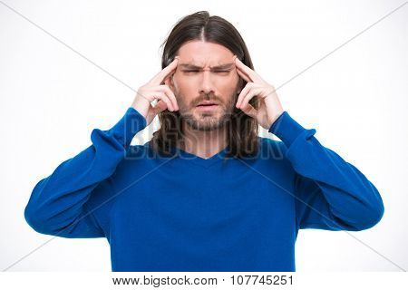 Young handsome man with long hair in blue sweater having headache and touching his temples by fingers