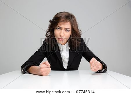 Mad aggressive young curly annoyed woman in black jacket sitting and pointing on you