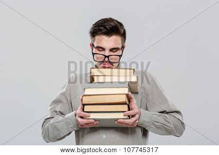 Exhausted handsome smart student in gray shirt and glasses holding books