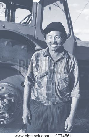 Smiling Mongolian Farmer Standing Next Tractor Concept