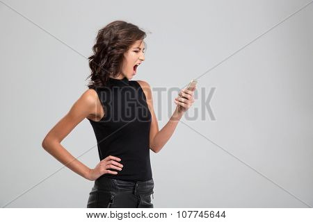 Mad angry young female screaming and using mobile phone