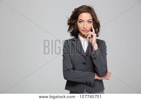 Portrait of confident beautiful curly young business woman in gray jacket