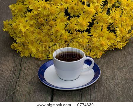 Cup Of Coffee And Beautiful Bouquet Of Flowers, On A Wooden Table