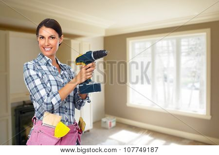Young woman with a drill. House renovation background.