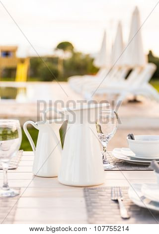 Elegant white tableware jugs,bowls, plates and wine glass set on table