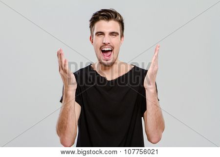 Portrait of young handsome carismatic man in black t-shirt screaming with hands up