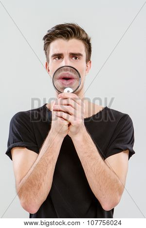 Handsome carismatic young freak man using magnifying glass