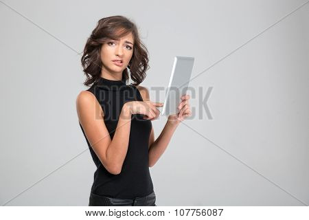 Disappointed annoyed young woman in black clothes using tablet