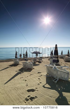Couple Stands Near Water In  Morning On  Beach Which Empty Deck-chairs Are Built On