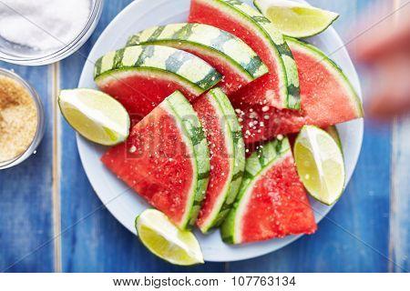 sprinkling salt on pile of watermelon slices