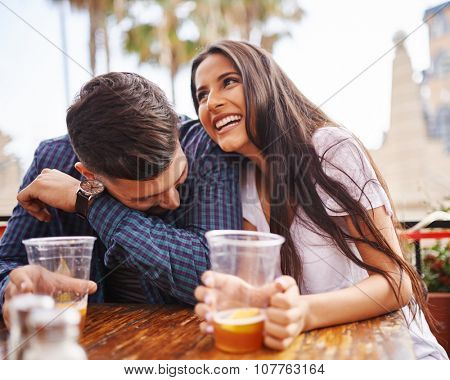 Hispanic couple laughing and having fun while drinking beer shot with selective focus