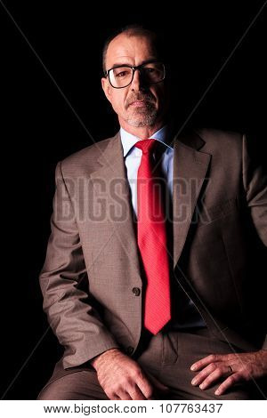 mature businss man sitting on a chair against black studio background
