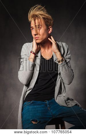 fashionable young man wearing rugged jeans and touching his neck pose while looking away
