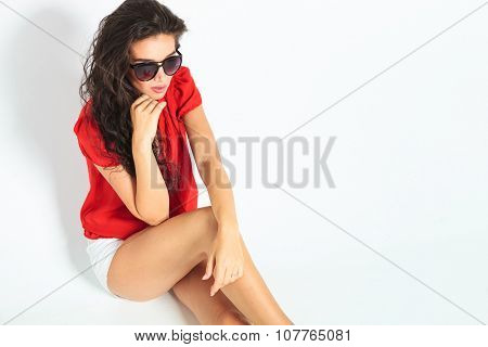 cute girl sitting with her legs crossed and thinking while touching her chin and looking away off the camera