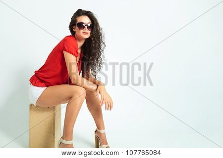 woman wearing sunglasses and high heels while sitting on a wooden box with her hands crossed