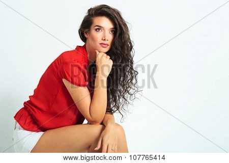 attractive woman sitting and resting her hands on her leg while looking up away off the camera