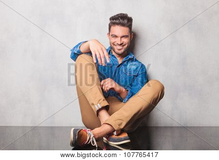 smiling man in denim shirt sitting legs crossed in studio background resting his arm on his leg