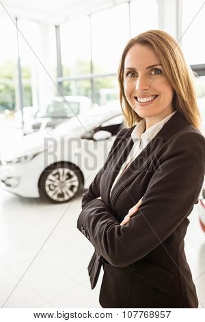 Smiling saleswoman standing with arms crossed at new car showroom